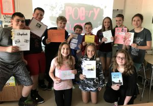 Middle school students pose with decorated poetry chapbooks