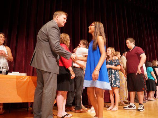 girl shakes man's hand