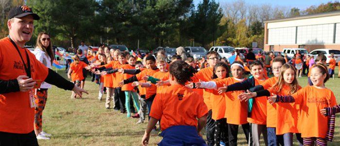 Teacher cheers on students finishing Monster Dash run