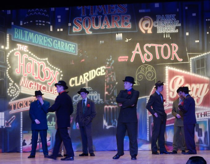 Seven boys dressed in suits act on stage