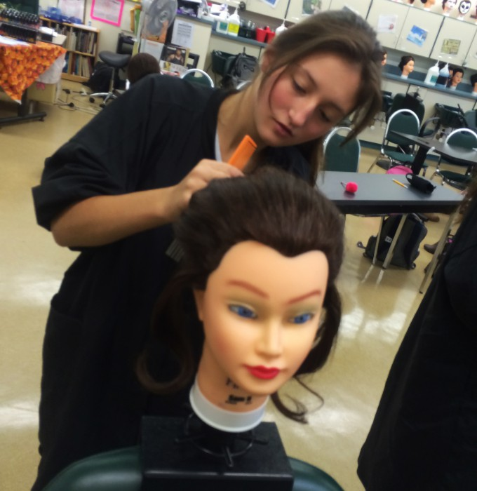 One student practicing cosmetology on mannequin