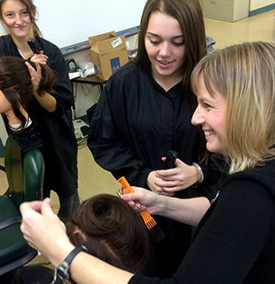 Students practicing cosmetology on mannequins
