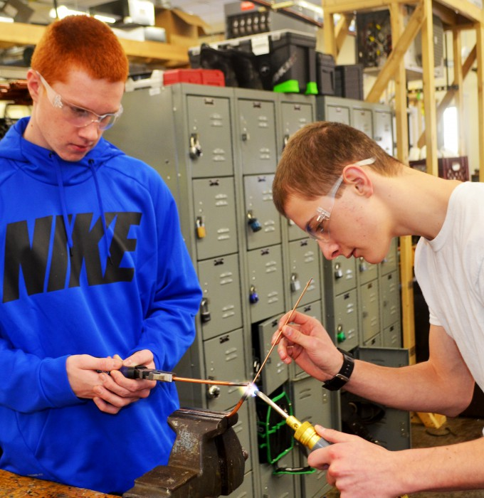 Two students working with welding tools