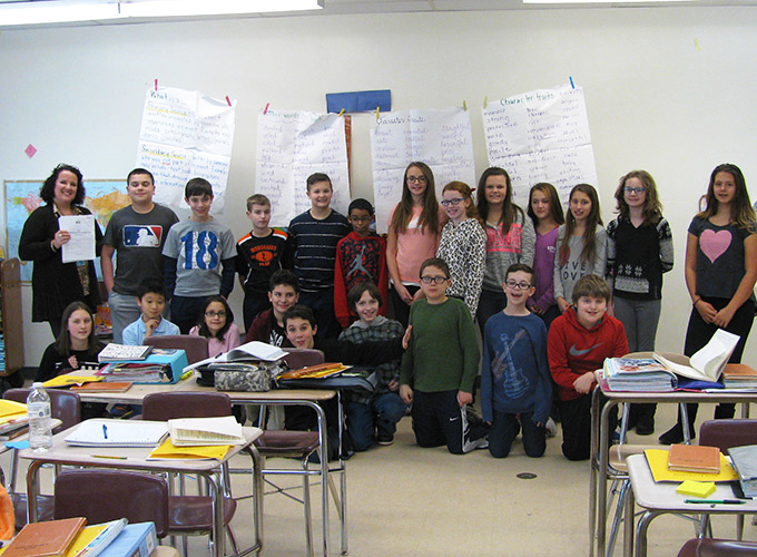 Middle school class posing in classroom