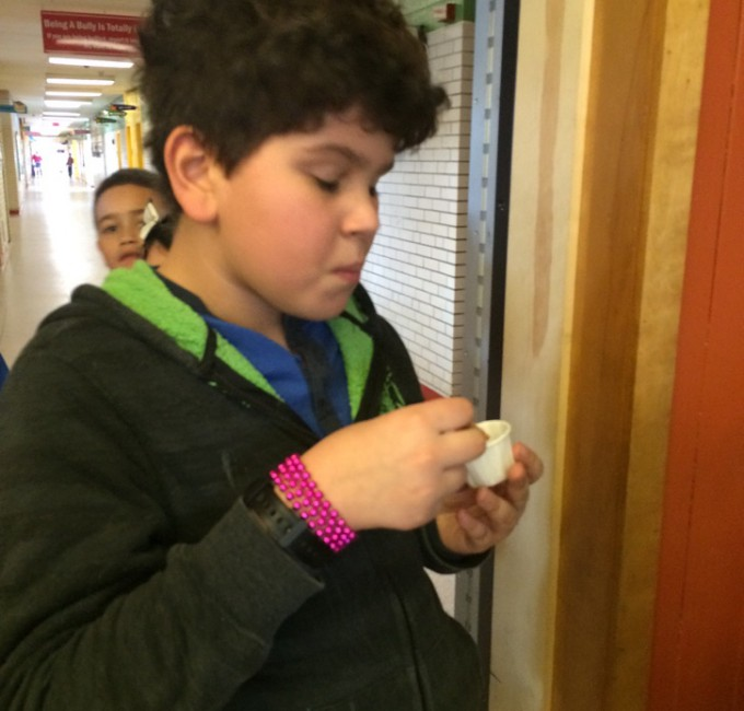 Student samples food from sampling cup