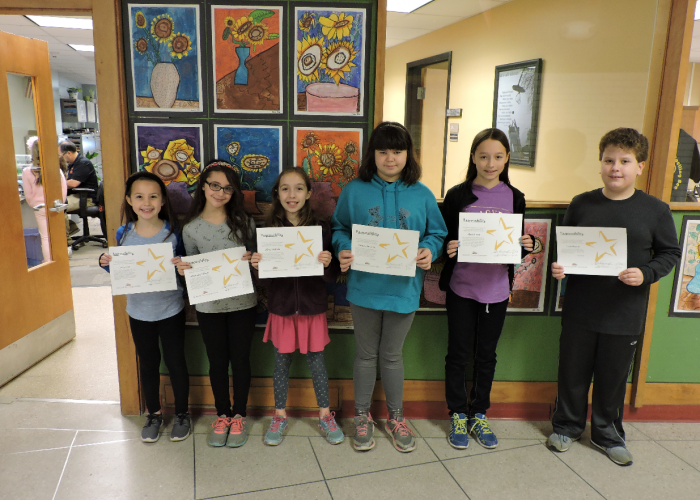 Students holding certificates honoring responsible traits