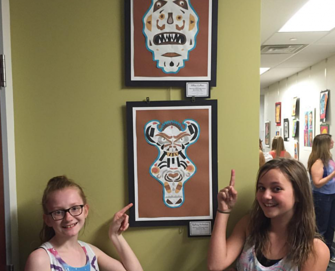 Students pointing to their artwork on the wall