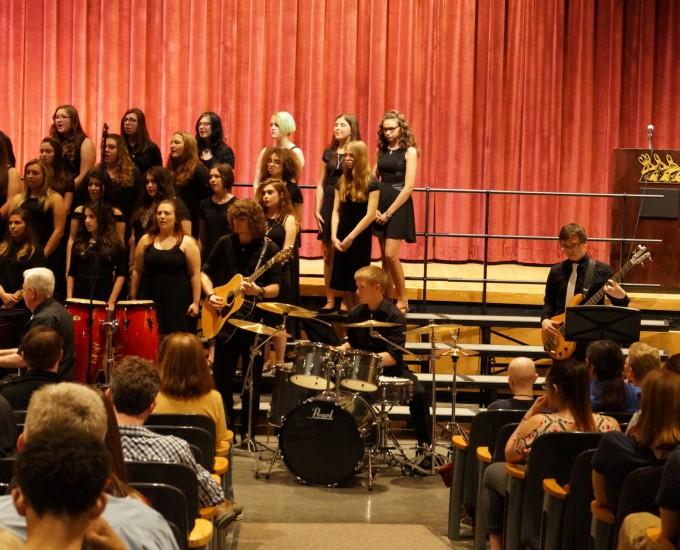 Student choir performs alongside drummer, guitar and bass player