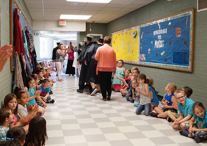 Elementary students watch graduates