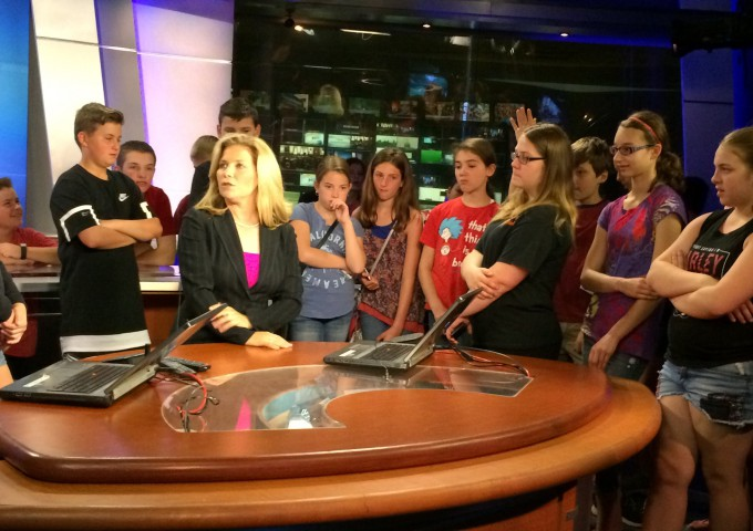 Middle school students talking to news anchor