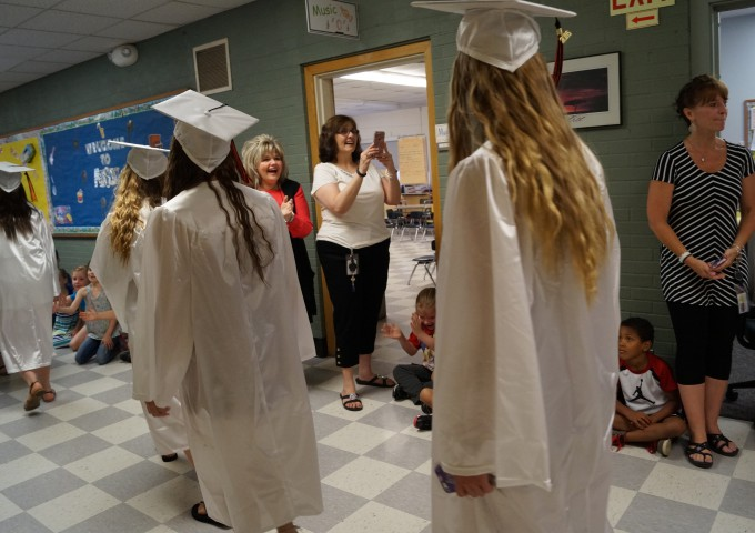 Students walk down hallways in caps and gowns