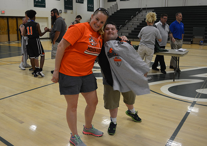 Coach and member of unified basketball team pose with tshirt