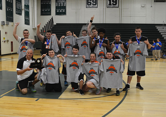 Unified basketball team members pose for group photo with t-shirts
