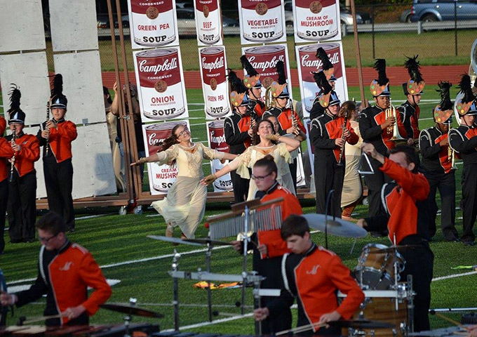 Color guard performs in field of marching band students