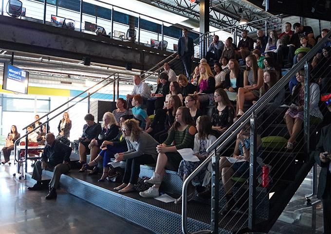 Audience members watch panel