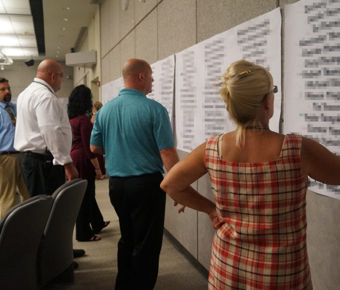 Faculty members look at lists of student names
