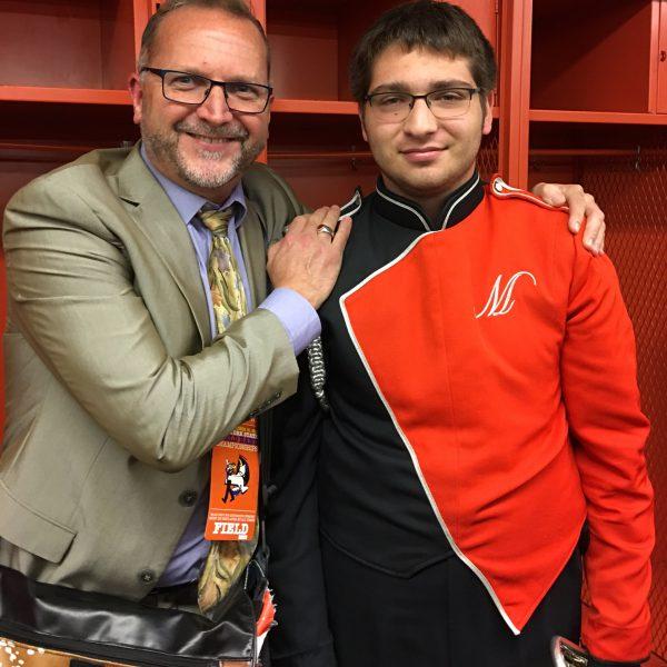 Band director Dan Jones poses with student