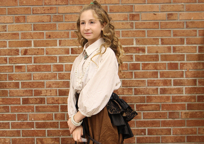 Student in historical garb poses for photo