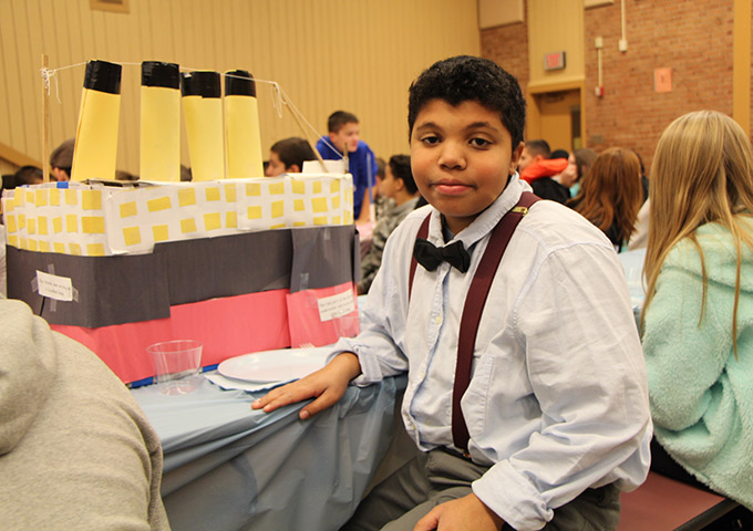 Student sits next to Titanic replica in costume