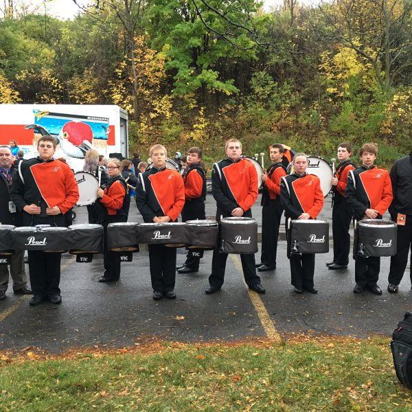 Student band members line up in parking lot