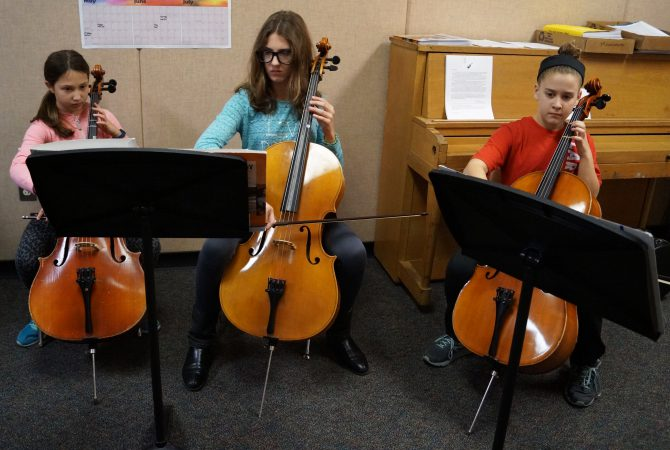 Three students playing cellos at music stands