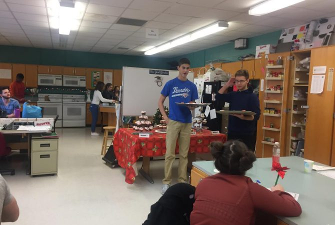 Pair of students presents cupcakes to judges