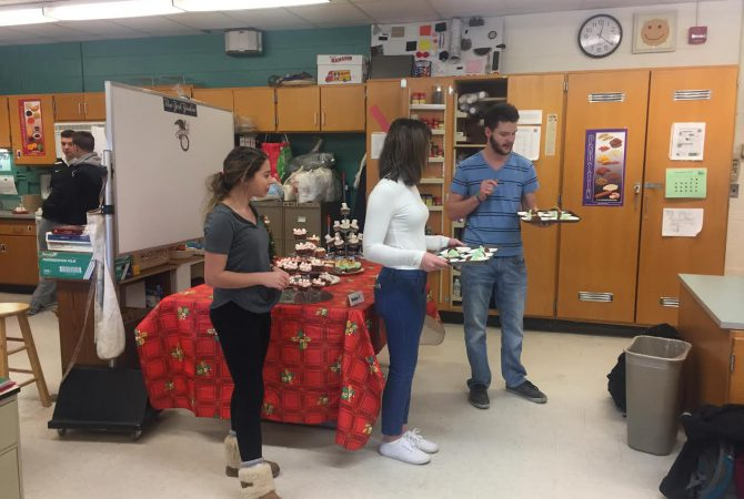 Trio of students presents cupcakes to judges