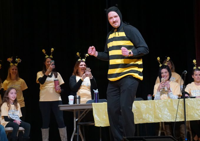 School administrator dressed up in bee costume walks in front of stage