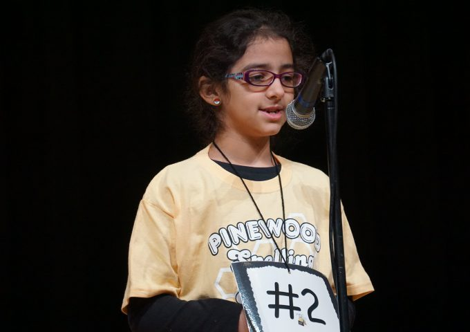 Spelling bee participant stands at microphone on stage