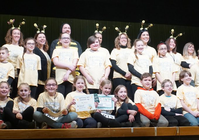 All spelling bee participants and judges pose for a group photo on stage