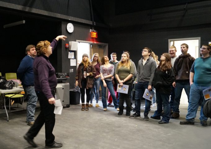 Students look up toward ceiling in blackbox theater