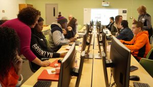Students sit at rows of computers with career mentors