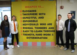 "Draper students stand by slogan on display in hallway that reads ""Draper is [a] welcoming atmosphere with respectful and responsible individuals who are original thinkers and ready to learn through strength, hard work and determination"""