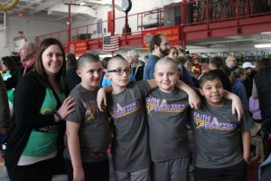 Students with shaved heads pose for photo at the fundraiser