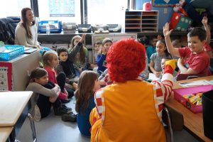 Ronald McDonald sits on floor near group of third-grade students who raise their hands as Ronald points at one student