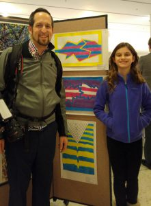 Teacher Steven Blais stands with student next to artwork on display