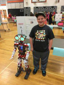 Student stands beside robot