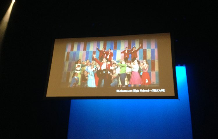 "Screen showing photo of Mohonasen students practicing in costume for ""Grease"""