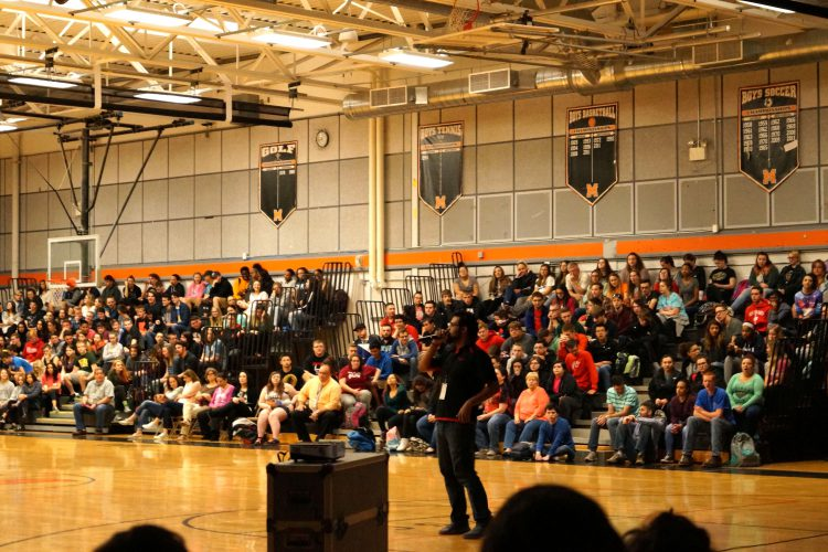 Man speaks to crowd of students sitting on bleachers in gymnasium