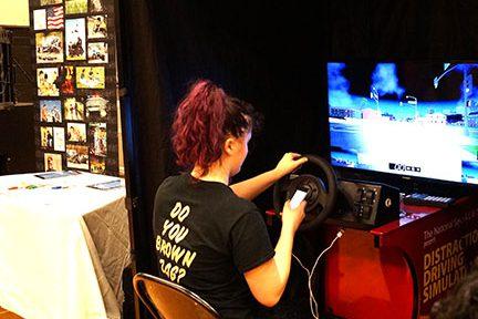 Girl sits at texting and driving simulation terminal