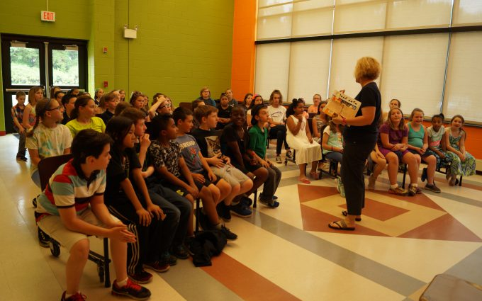 Students watch teacher while sitting in rows