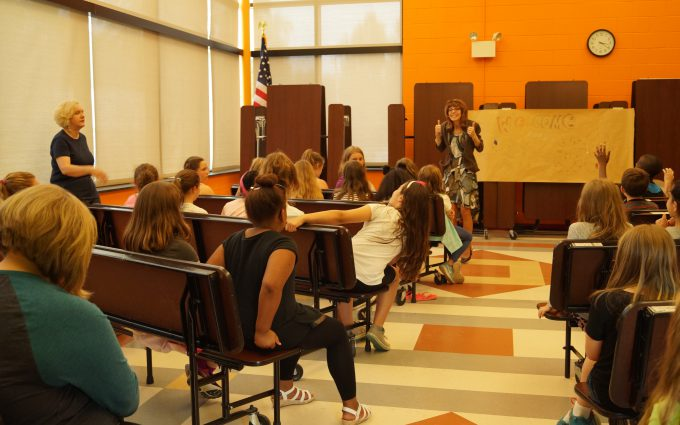 Composer stands in front of students, giving thumbs-up