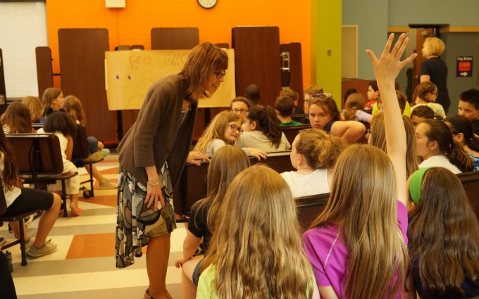 Composer talks to student sitting in row