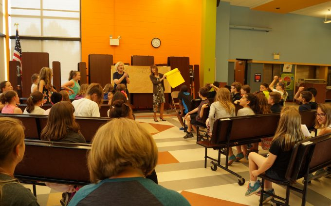 Composer holds up large yellow card, a gift from students
