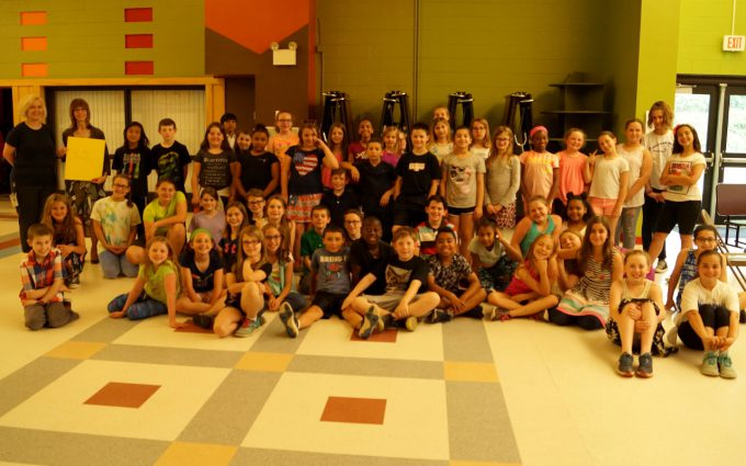 Students, composer and teacher pose for group photo in cafeteria
