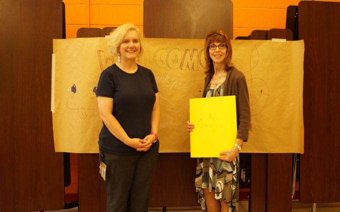 Orchestra teacher and composer pose for photo, holding gift from students