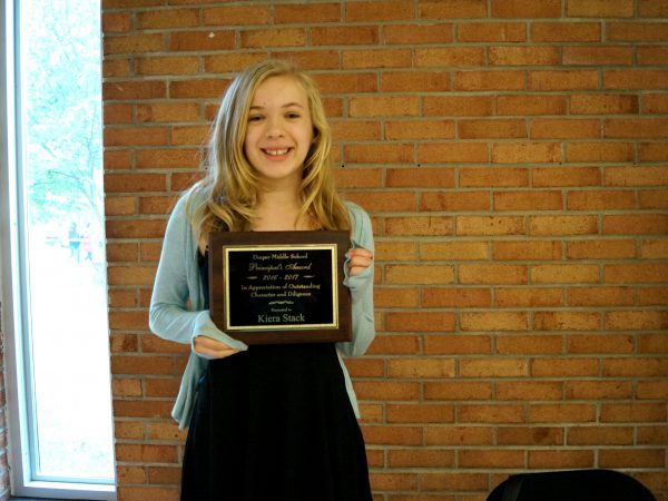 girl holds plaque while smiling at camera