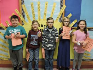 5 elementary school students stand in a row holding their certificates