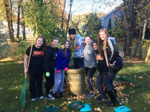 A group of middle school students smile and hold rakes around a bag of leaves