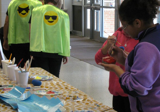 Two adults display superhero cape while two students paint Kindness rocks